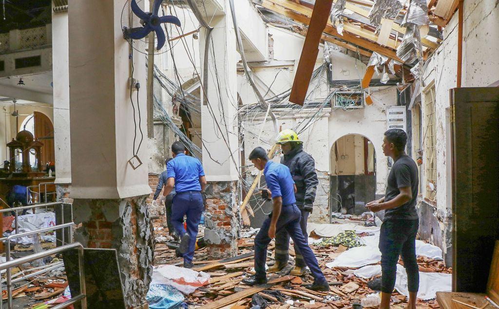 Πυροσβέστης και άνδρες σε κατεστραμμένο χώρο από το εσωτερικό του ναού στη Σρι Λάνκα