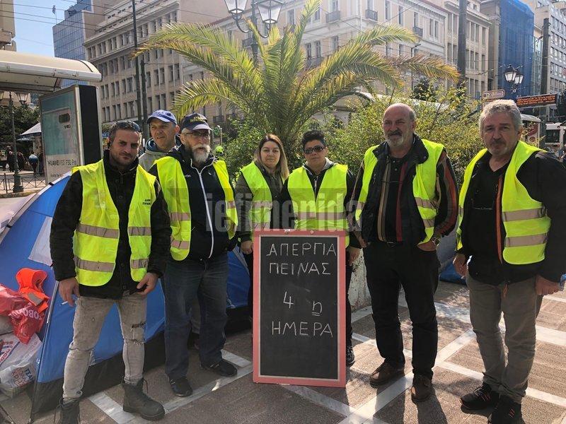 Οι συμβασιούχοι στέκονται στο πεζοδρόμιο μπροστά από ταμπέλα που γράφει: Απεργία πείνας για 4η ημέρα