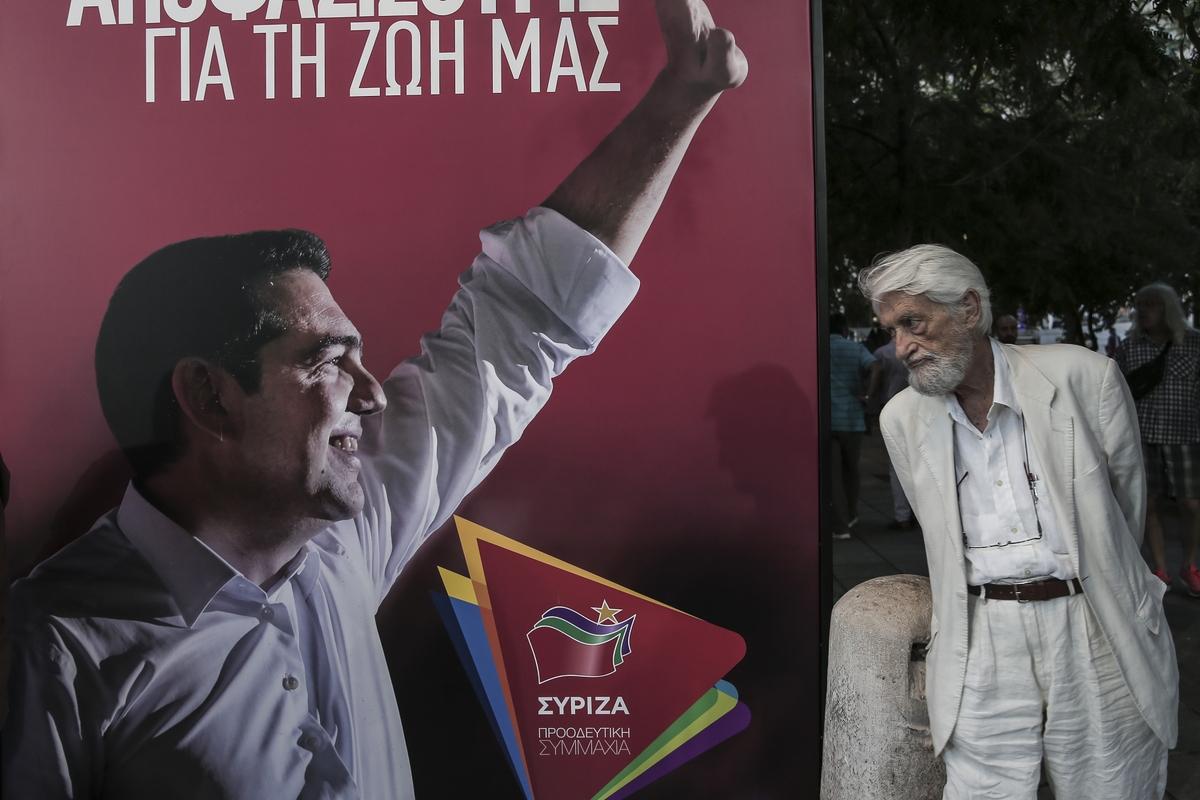 Ενας ηλικιωμένος κοιτάζει μια προεκλογική αφίσα του ΣΥΡΙΖΑ με τον Αλέξη Τσίπρα