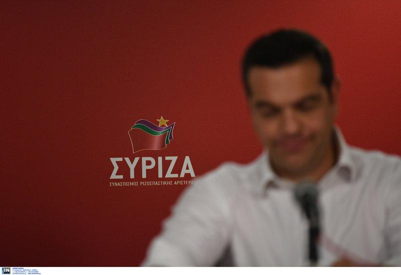 Ο Αλέξης Τσίπρας με φόντο το σήμα του ΣΥΡΙΖΑ