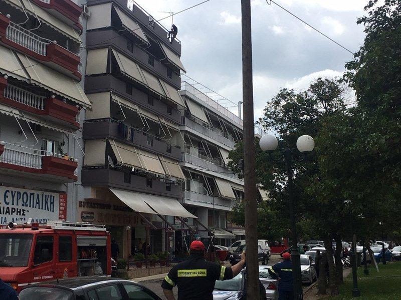 Πυροσβέστες κάτω από την πολυκατοικία όπου βρίσκεται ο νεαρός.