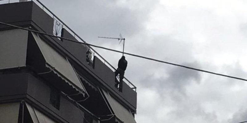 Ο νεαρός άνδρας σκαρφαλωμένος στην άκρη της ταράτσας, απειλώντας να πέσει