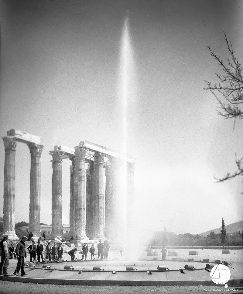 Στιγμιότυπο από την τελετή εγκαινίων του νέου δικτύου ύδρευσης των πόλεων Αθηνών, Πειραιώς και περιχώρων, στους Στύλους του Ολυμπίου Διός, 03 Ιουνίου 1931. Η Ελληνική Εταιρεία Υδάτων διαφημίζεται μέσω της τοποθέτησης πιδάκων νερού στην τελετή των εγκαινίων/Φωτογραφία: Ιστορικό Αρχείο ΕΥΔΑΠ