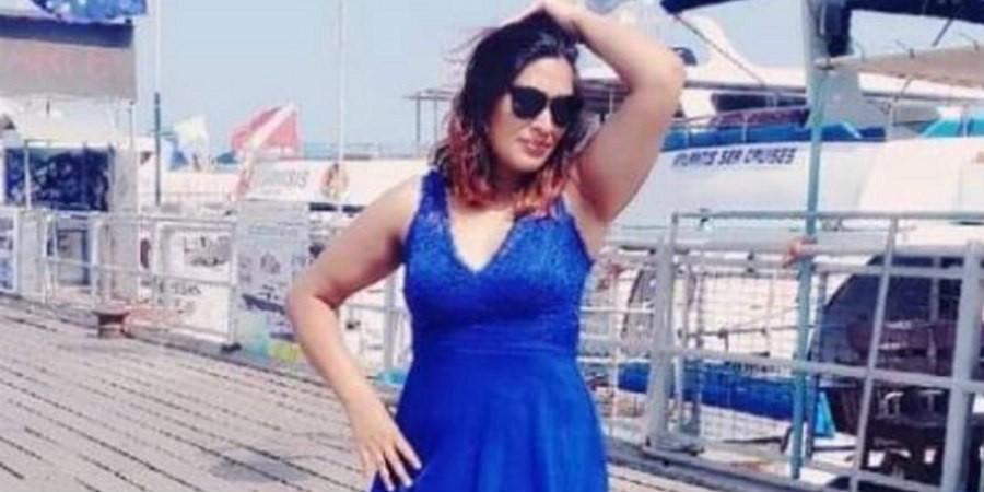 Γυναίκα με μπλε φόρεμα και γυαλιά ηλίκου ποζάρει στο φακό. Το θύμα του serial killer