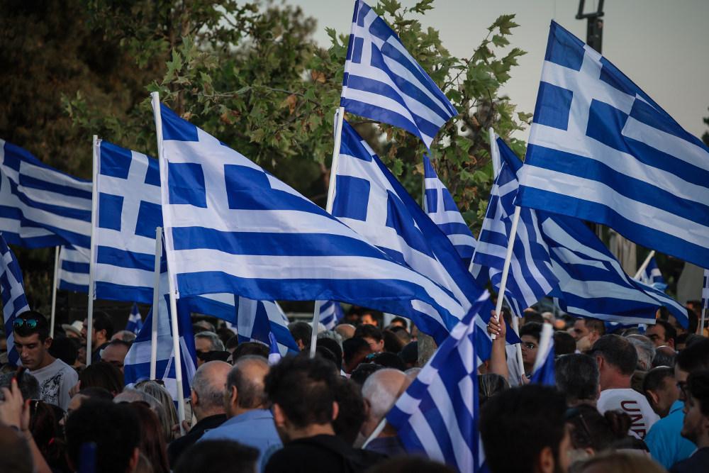 Οι οπαδοί της Νέας Δημοκρατίας κρατούν ελληνικές σημαίες αναμένοντας τον Κυριάκο Μητσοτάκη