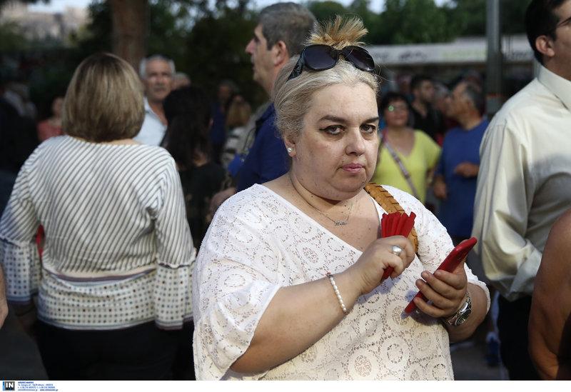 Μια κυρία με κόκκινη βεντάλια και κόκκινο κινητό