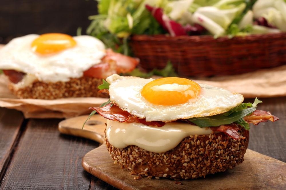 Αυγό τηγανητό πάνω σε ψωμάκι, λιωμένο τυρί, μπέικον και ρόκα