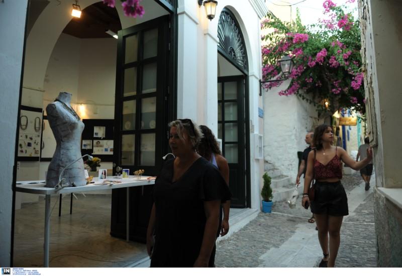Τουρίστες σε σοκάκια νησιού με μαγαζιά τουριστικών ειδών