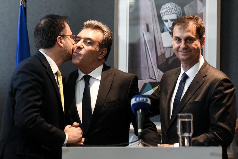 Ο νέος υφυπουργός Τουρισμού Μάνος Κόνσολας ανταλλάσσει ασπασμό με τον Θ. Θεοχαρόπουλο υπό το βλέμμα του νέου υπουργού Τουρισμού Χάρη Θεοχάρη