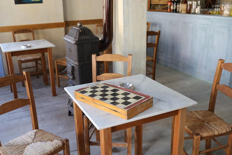 Εικόνα από το καφενείο στη σειρά «Άγριες Μέλισσες» με τα τραπέζια και ένα τάβλι