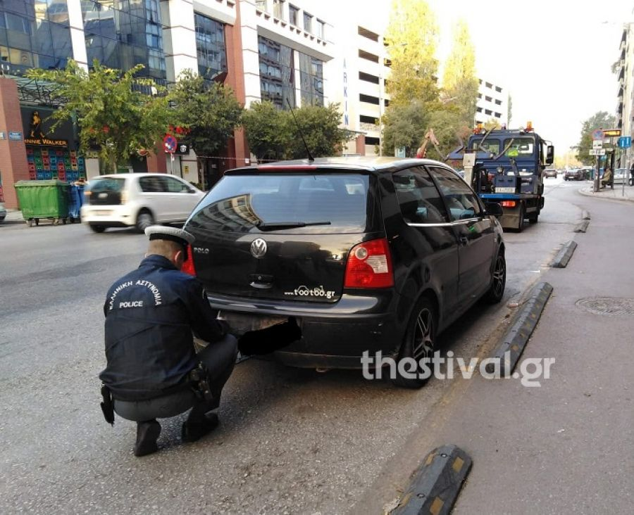 Αστυνομικός αφαιρεί την πινακίδα από παράνομα παρκαρισμένο ΙΧ