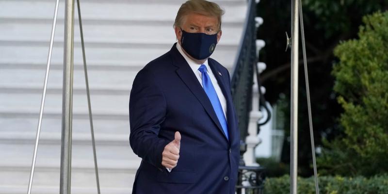 Ο Τραμπ καταβεβλημένος και με μάσκα, σηκώνει προς τους δημοσιογάφους τον αντίχειρα για να δείξει ότι όλα είναι καλά
