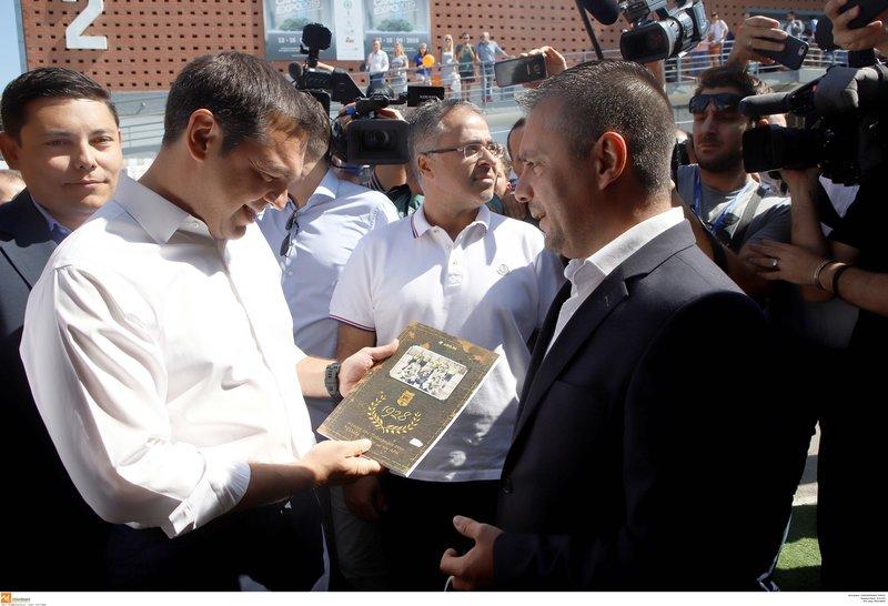 Ο Αλέξης Τσίπρας κρατά το βιβλίο με την ιστορία του Αρη που του έδωσαν στη ΔΕΘ
