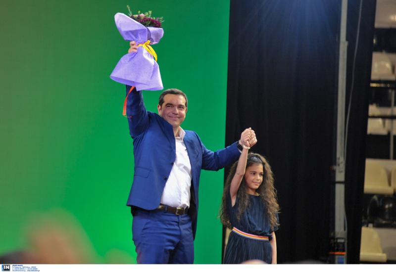Ο Αλέξης Τσίπρας σε πράσινο φόντο σηκώνει το μπουκέτο με τα λουλούδια και το χέρι του κοριτσιού που του τα πρόσφερε
