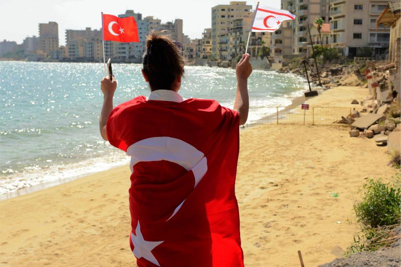 Γυναίκα με τουρκικές σημαίες στην παραλία στα Βαρώσια