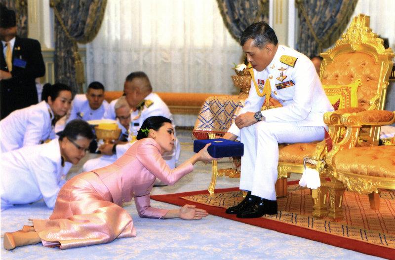 Η βασίλισσα της Ταϊλάνδης, Σουτίντα, πεσμένη στα πόδια του βασιλιά, δέχεται τα δώρα του.