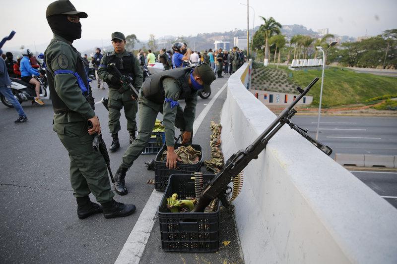Στρατιώτες τοποθετούν όπλα και πυρομαχικά σε γέφυρα στη Βενεζουέλα / Φωτογραφία: AP