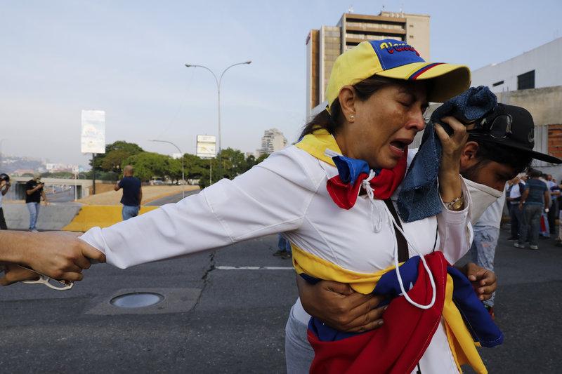 Γυναίκα προσπαθεί να αναπνεύσει από τα δακρυγόνα που πέφτουν σωρηδόν