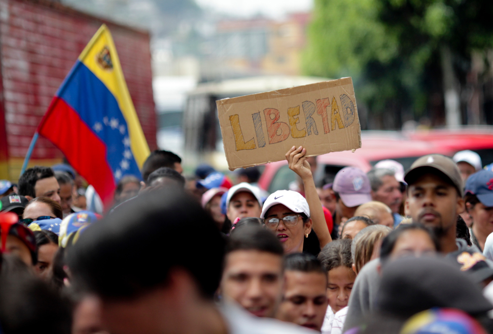 Κόσμος στο δρόμο με πλακάτ και σημαίες διαδηλώνει στη Βενεζουέλα