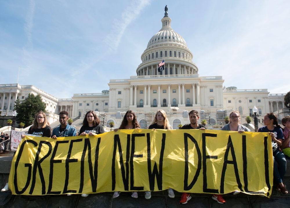 Νέοι υψώνουν πανό για μια νέα «πράσινη συμφωνία» μπροστά από το Καπιτώλιο στην Ουάσιγκτον των ΗΠΑ / Φωτογραφία: AP Photos