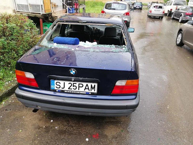 Ενα αυτοκίνητο με σπασμένα παράθυρα από το χαλάζι