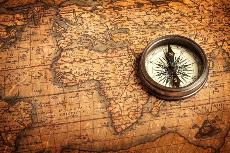 μία πυξίδα πάνω σε έναν παγκόσμιο χάρτη