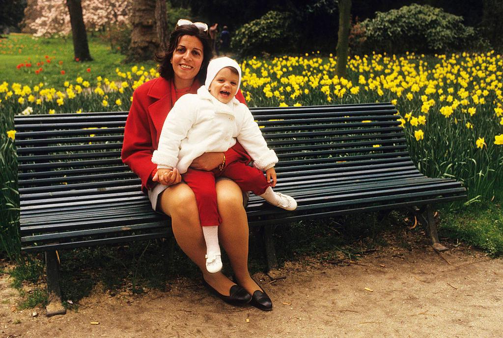 Η Χριστίνα Ωνάση με κόκκινο σακάκι και γυαλιά ηλίου κρατά την Αθηνά μωρό σε παγκάκι