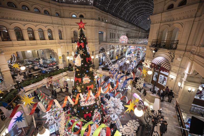 Οι άνθρωποι περπατούν σε πολυκατάστημα διακοσμημένο για τους εορτασμούς των Χριστουγέννων και της Πρωτοχρονιάς, που είναι σχεδόν άδειο λόγω της πανδημίας του κορωνοϊού στη Μόσχα