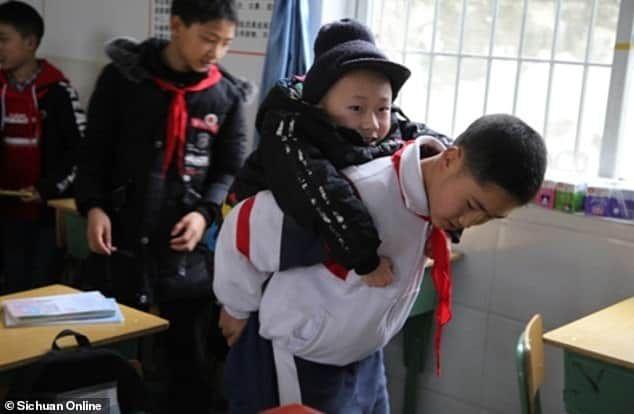 Οι δάσκαλοί του καμαρώνουν για τον 12χρονο Ζου, που εικονίζεται εδώ να μεταφέρει τον ανάπηρο φίλο του στο θρανίο του /Φωτογραφία: Sichuan Online