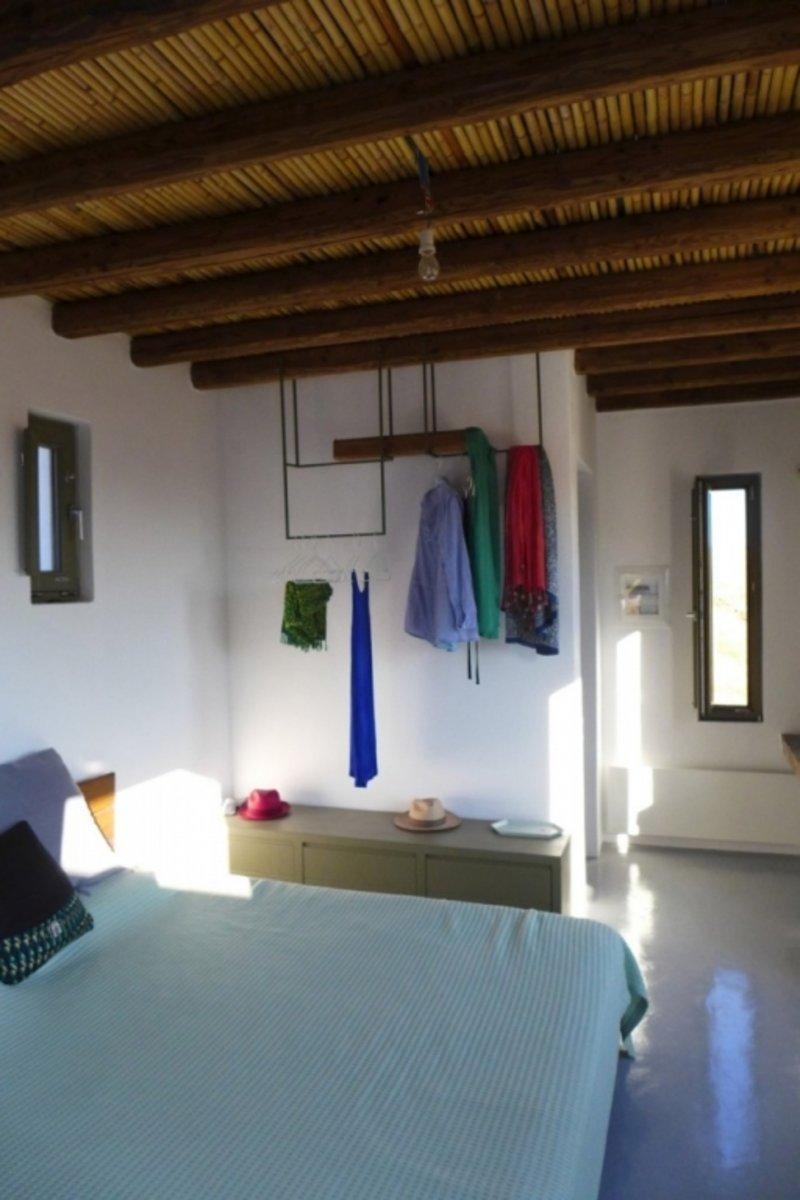 Το μίνιμαλ υπνοδωμάτιο με ένα κρεβάτι και μια κρεμάστρα για τα ρούχα