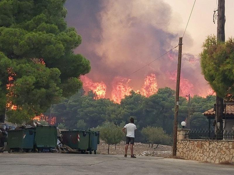 Ανήμπορος ένας κάτοικος της Ζακύνθου κοιτά τις φλόγες που κατακαίνε δίπλα στα σπίτια